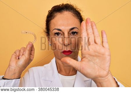 Middle age senior dentist woman holding clear aligner for teeth correction with open hand doing stop sign with serious and confident expression, defense gesture