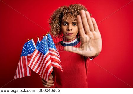 Young african american patriotic curly woman holding united states flags over red background with open hand doing stop sign with serious and confident expression, defense gesture
