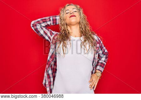 Young beautiful blonde woman wearing casual shirt standing over isolated red background Suffering of neck ache injury, touching neck with hand, muscular pain
