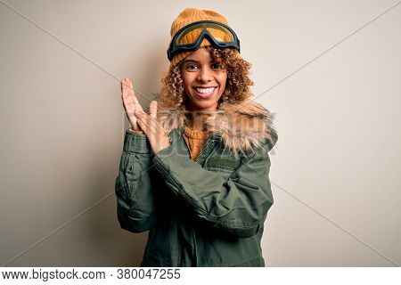Young african american skier woman with curly hair wearing snow sportswear and ski goggles clapping and applauding happy and joyful, smiling proud hands together