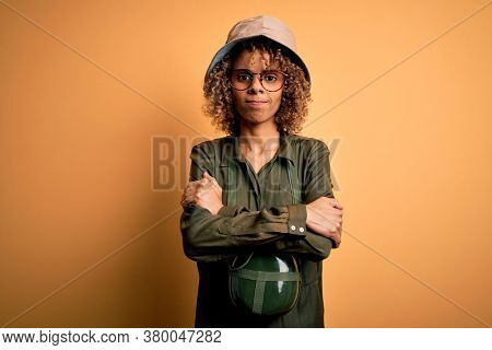 Young african american tourist woman on vacation wearing explorer hat and water canteen skeptic and nervous, disapproving expression on face with crossed arms. Negative person.