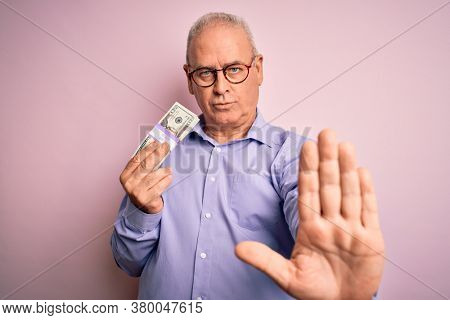 Middle age hoary man holding bunch of dollars banknotes over isolated pink background with open hand doing stop sign with serious and confident expression, defense gesture