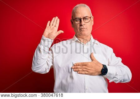 Middle age handsome hoary man wearing casual shirt and glasses over red background Swearing with hand on chest and open palm, making a loyalty promise oath