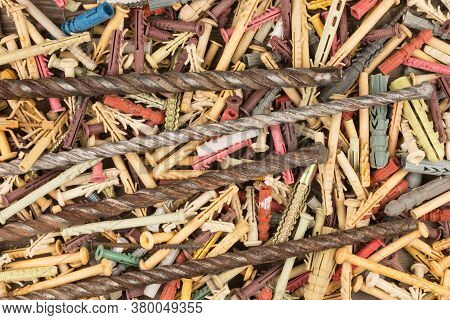 Old Drills For Drilling Concrete Lies On A Pile Of Dowels. Construction Background. Top View