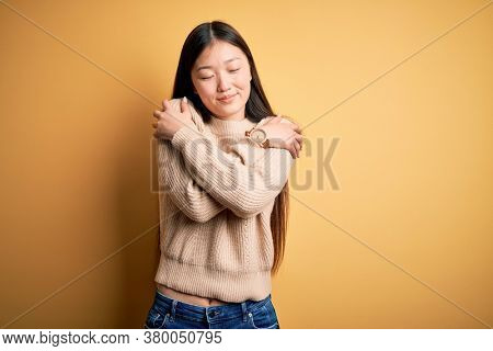 Young beautiful asian woman wearing casual sweater over yellow isolated background Hugging oneself happy and positive, smiling confident. Self love and self care