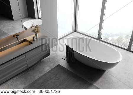 Top View Of Stylish Bathroom With Gray Walls, Concrete Floor, Double Sink Standing On Wooden Cabinet