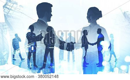Silhouettes Of Businessman And Businesswoman Shaking Hands In Blurry Modern Office With Their Collea
