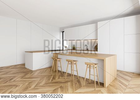 Corner Of Modern Kitchen With White And Brick Walls, Wooden Floor, White Cupboards And Bar With Wood