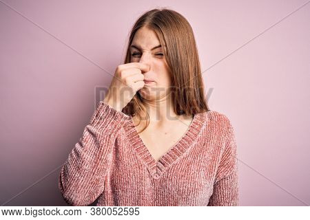 Young beautiful redhead woman wearing casual sweater over isolated pink background smelling something stinky and disgusting, intolerable smell, holding breath with fingers on nose. Bad smell