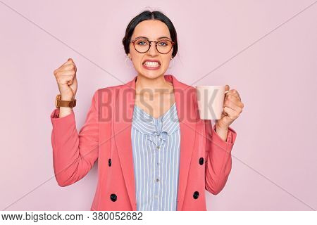 Young beautiful businesswoman with blue eyes wearing glasses drinking pink mug of coffee annoyed and frustrated shouting with anger, crazy and yelling with raised hand, anger concept