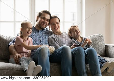 Happy Bonding Family Of Four Watching Movie Together Indoors.