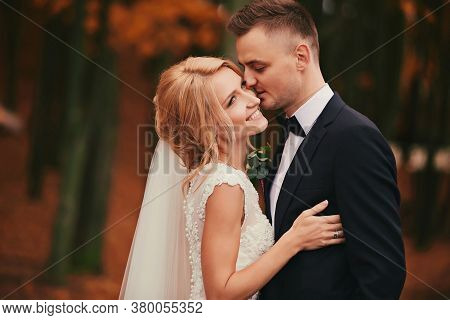 The Groom Kisses Bride In Autumn Park. Beautiful Woman With Bouquet Of Flowers. The Groom In A Black