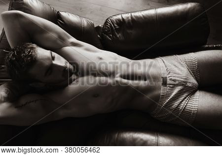 Portrait Of Attractive Shirtless Muscular Man With Beard And Sixpack Abs Lying In Leather Armchair,