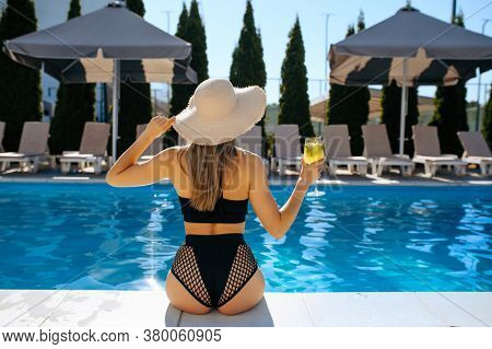 Slim woman with coctail at the poolside, back view