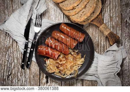 Fried Sausage With Onion On Black Plate. Top View.