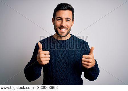 Young handsome man with beard wearing casual sweater standing over white background success sign doing positive gesture with hand, thumbs up smiling and happy. Cheerful expression and winner gesture.