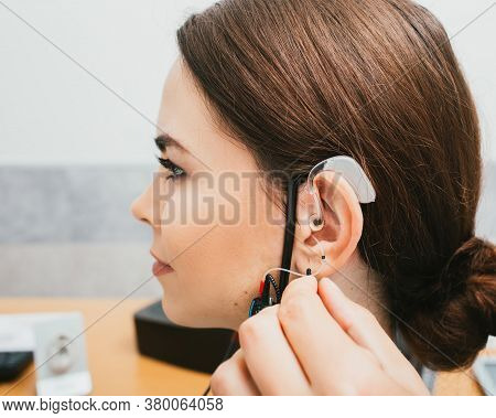 Audiologist Programming Hearing Aid Acoustic Response Using The Software. Young Woman Getting Hearin