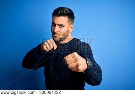 Young handsome man wearing casual sweater standing over isolated blue background Punching fist to fight, aggressive and angry attack, threat and violence