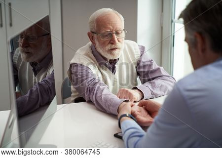 Elderly Man Having His Wrist Tendons Examined By A Doctor