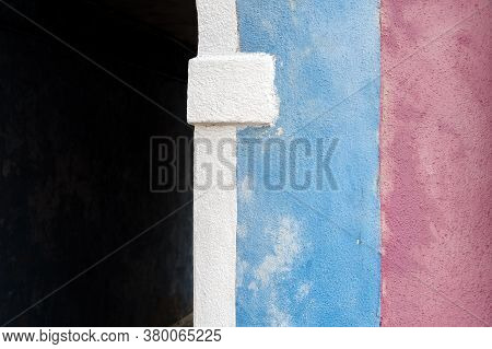 Light Blue And Pink Wall Next To White Arch And Dark Passageway