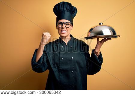 Young beautiful brunette chefwoman wearing cooker uniform and hat holding tray with dome annoyed and frustrated shouting with anger, crazy and yelling with raised hand, anger concept