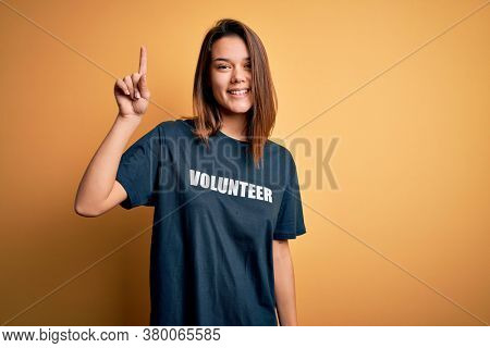 Young beautiful brunette girl doing volunteering wearing t-shirt with volunteer message word pointing finger up with successful idea. Exited and happy. Number one.