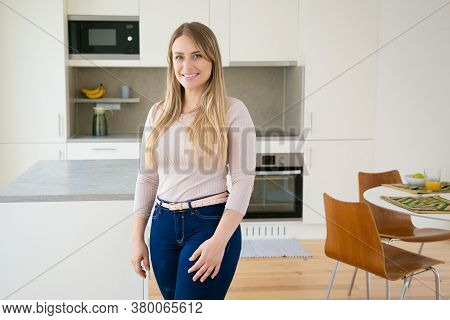 Happy Pretty Fair Haired Young Woman Posing In Kitchen, Looking At Camera And Smiling. Medium Shot.