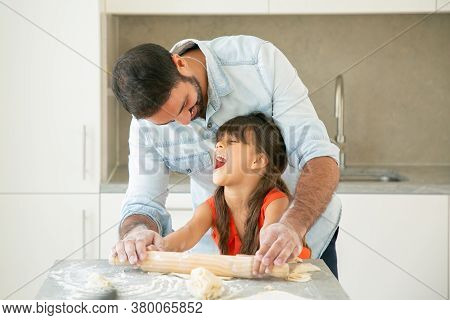 Excited Girl And Her Happy Dad Rolling And Kneading Dough On Kitchen Table With Flour Messy. Father