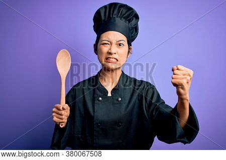 Young beautiful chinese chef woman wearing cooker uniform and hat holding wooden spoon annoyed and frustrated shouting with anger, crazy and yelling with raised hand, anger concept