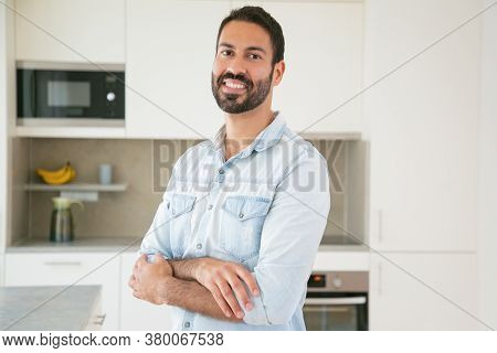 Happy Handsome Dark Haired Latin Man Posing With Arms Folded In Kitchen, Looking At Camera And Smili