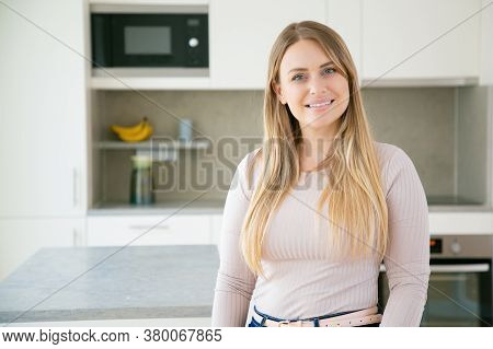 Cheerful Beautiful Fair Haired Young Woman Posing In Kitchen, Looking At Camera And Smiling. Medium