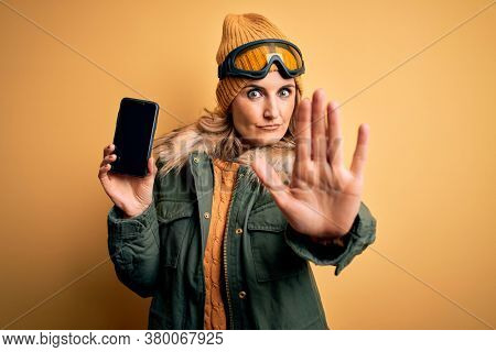 Middle age blonde skier woman wearing ski goggles holding smartphone showing screen with open hand doing stop sign with serious and confident expression, defense gesture
