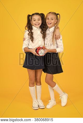 Schoolgirls And Alarm Clock. Children School Pupils Adorable Formal Uniform Outfit. Kids Hold Alarm