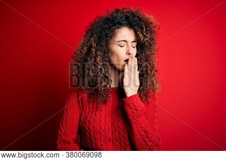 Young beautiful woman with curly hair and piercing wearing casual red sweater bored yawning tired covering mouth with hand. Restless and sleepiness.