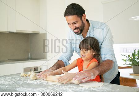 Happy Dad And Daughter Rolling Dough On Kitchen Table With Flour Messy. Father Teaching Girl To Bake
