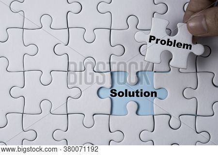 Hand Holding And Putting Problem Jigsaw Puzzle To Solution. Problem Solving Concept.