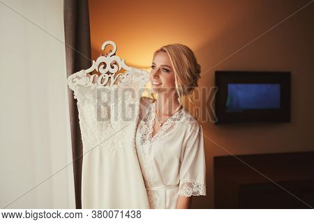 Young Bride With A Wedding Dress In Her Hands. Lovely Sensual Bride. Brides Morning