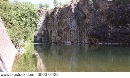 View Of A Flooded And Old Limestone Mine From 19. Century With Beautiful Reflections Of Rocks And Tr