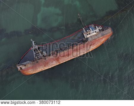 Top View Of An Old Tanker That Ran Aground And Overturned On The Shore Near The Coast. A Storm-swept