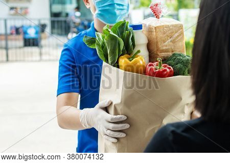 Hand Of Food Delivery Service Man Wearing Protection Face Mask Holding Fresh Food Set Paper Bag To C