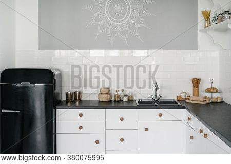 White Modern Kitchen With Drawers, Cupboards, Utensils, Sink And Water Tap On Countertop Near Retro