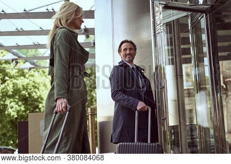 Mirthful Man With A Suitcase Holding A Hotel Door Open For His Tarvel Companion