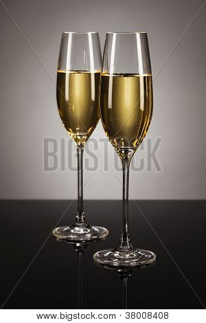 two glasses of champagne on a mirror