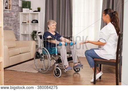 Patient Using Dumbbells For Rehabilitation Sitting On Wheelchair In Living Room With Nurse. Disabled