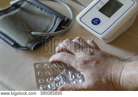 Male Hand Holds Blister With Pills On The Table. Medical Electronic Automatic Blood Pressure Monitor