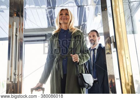 Mirthful Couple Entering The Hotel And Smiling