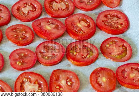 Baking Tray With Tomatoes Cut Into Chicken. The Process Of Drying Ripe Vegetables In The Oven. Dried