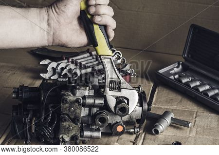 Repair Of A Diesel Fuel Pump Of A High Pressure. Car Mechanic Unscrews Bolts With A Wrench. Car Serv