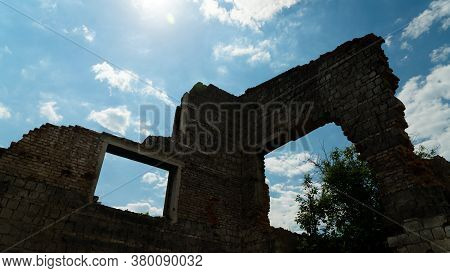 Rift In A Brick Wall. Close-up. Ruined Red Brick Wall. The Wreckage Of The Wall Against The Sky. The