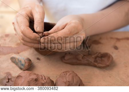 Close-up Of Childrens Hands Working With Clay. The Child Makes Dishes And Other Crafts. Pottery. Con